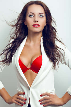 red bra: closeup vertical portrait of sexual brunette woman with flying hair over white wall
