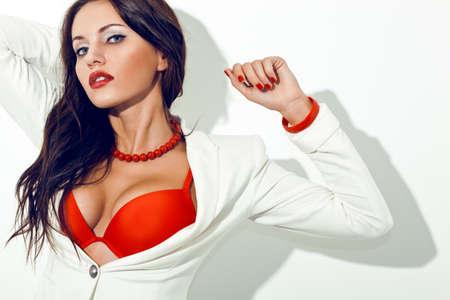 red bra: sexy brunette woman wearing red bra posing near white wall Stock Photo
