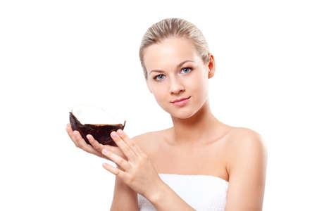 blonde woman with perfect skin holding coconut, spa and cosmetics theme photo