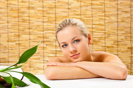 beautiful blond woman laying on table  with bamboo and coconut over bamboo mat background Stock Photo - 14274556