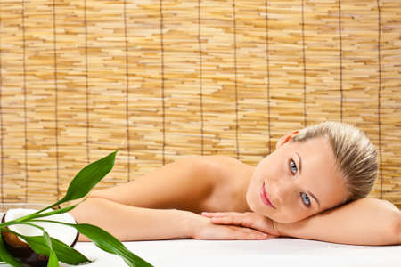 beautiful blond woman laying on table  with bamboo and coconut over bamboo mat photo