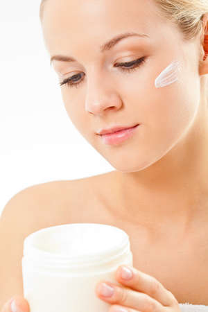 closeup blond woman portrait with cream on face over white background photo