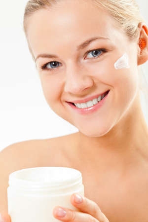 closeup blond smiling woman portrait with cream on face over white background photo