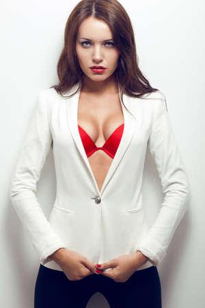 白い壁の近くのジャケットを保持している性的なブルネットの女性