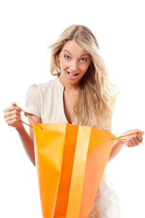 opened bag: surprised blonde woman holding opened shopping bag