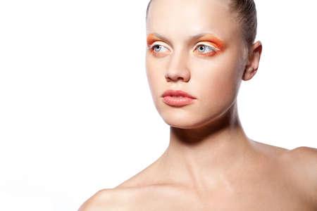 beautiful woman with creative orange makeup over white photo