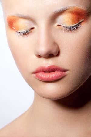 closed up: beautiful woman with creative orange makeup over white, closed eyes