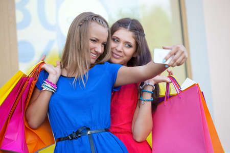 two woman taking pictures of themselves with phone camera photo