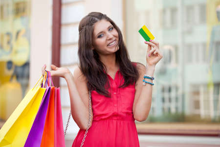 brunette woman holding credit card and bags photo