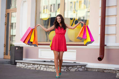 happy brunette woman walking with shopping bags photo