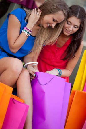 Two beautiful girls show each other the purchase photo
