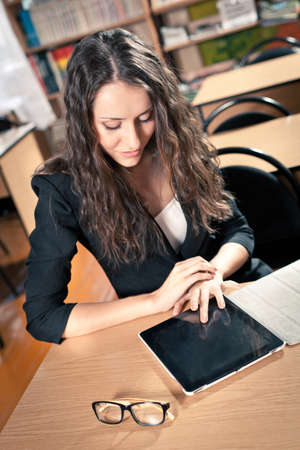 woman sitting at reading hall and touching tablet pc photo