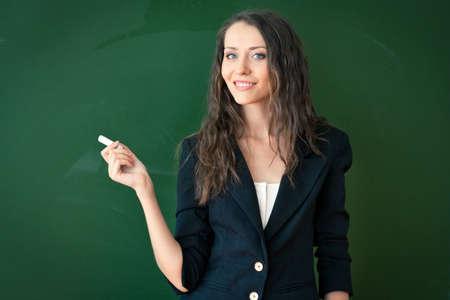 Frau stehend und halten Kreide über Tafel