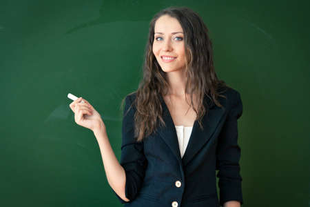 woman standing and holding chalk over chalkboard