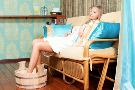 woman relaxing on sofa in spa salon photo