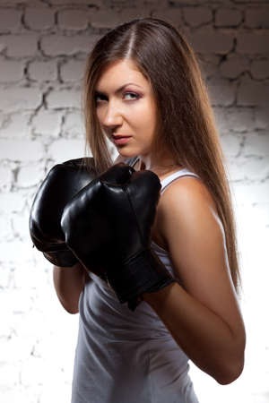 brunette woman wearing boxer gloves over brick wall with flying hair photo