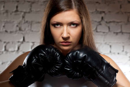 brunette woman wearing boxer gloves over brick wall with photo