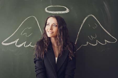 Mädchen über Tafel mit lustigen Engelsflügeln und Heiligenschein Standard-Bild