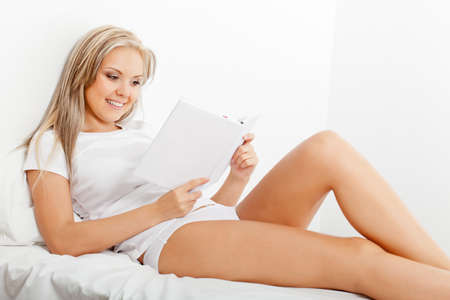 beautiful blonde woman reading book in bed and smiling photo
