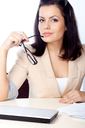 brunette businesswoman holding eyeglasses and looking at camera photo