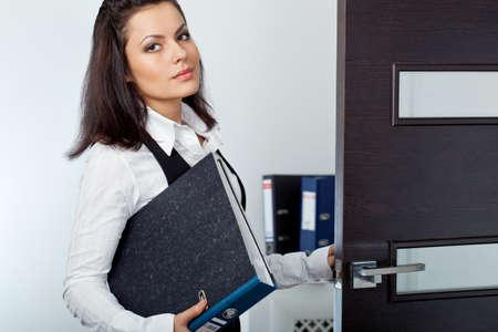 abriendo puerta: empresaria morena abriendo la puerta de color marrón oscuro Foto de archivo