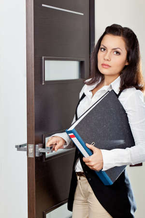 brunette businesswoman holding file and opening the dark brown door photo