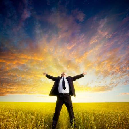 libertad: hombre de negocios feliz de pie en el campo antes de la puesta del sol Foto de archivo