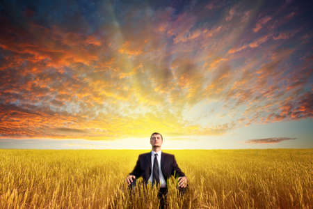 businessman sitting on filed in lotus pose, sunset time photo