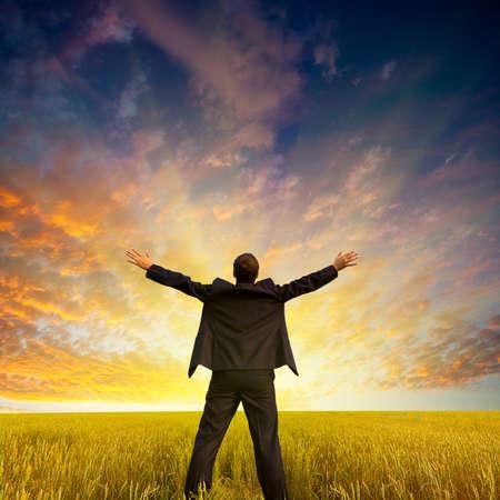 Happy Geschäftsmann stehend auf dem Feld, um den Sonnenuntergang zu Gesicht Standard-Bild