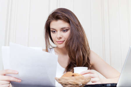 eats: Happy woman seated at her desk and reading documents during a break Stock Photo
