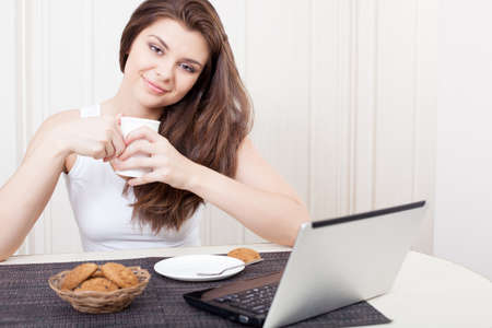 Happy woman seated at her desk in front of her laptop computer taking a break enjoying tea and cookies photo