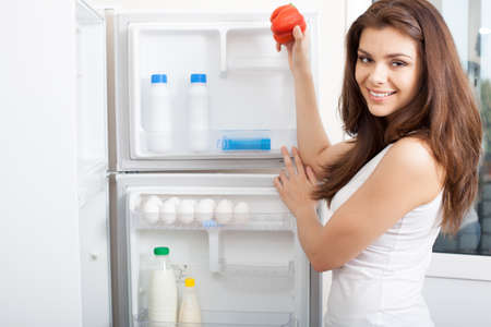 beverage fridge: happy beautiful Woman searching in her fridge for fresh ingredients to prepare a meal