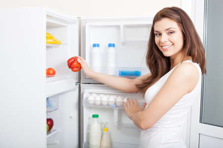 stocked: Woman taking red sweet pepper from her fridge, looking at camera