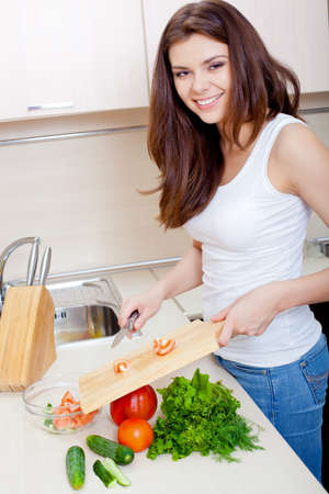 busty woman: happy smiling woman  puts tomatoes for salad  in a bowl Stock Photo