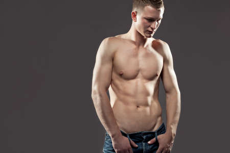 Sexy macho shirtless man with a muscular body posing in jeans with his thumbs hooked in the belt loops, looking down Stock Photo - 15389629