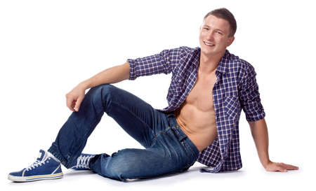 unbuttoned: sexy handsome sitting man posing in casual jeans and unbuttoned shirt, copy space