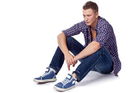 sexy hombre guapo sentado posando en jeans casuales y una camisa desabotonada Foto de archivo