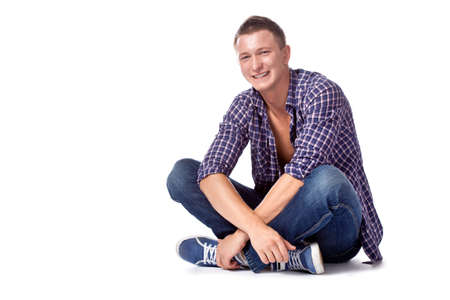 unbuttoned: sexy smiling handsome sitting man posing in casual jeans and unbuttoned shirt