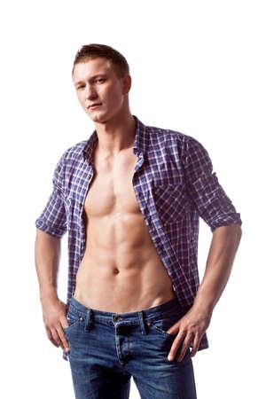 shirt unbuttoned: sexy uomo bello che propone in jeans casual e camicia sbottonata, guardando a porte chiuse Archivio Fotografico