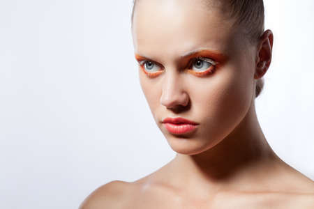 beautiful woman with creative orange makeup over white photo