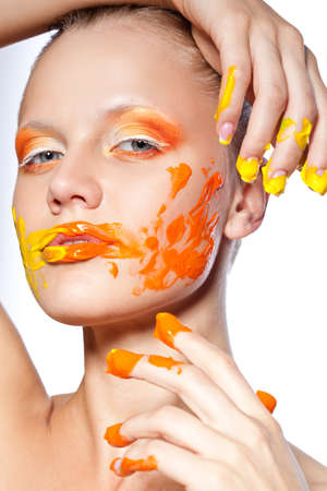 beautiful woman with creative orange makeup  and paints on her face and fingers photo