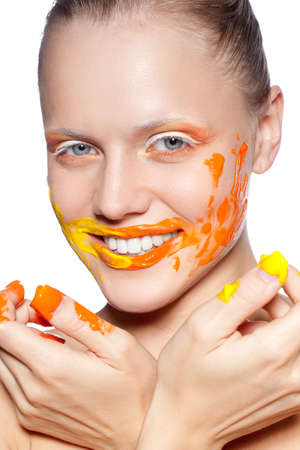 smiling happy woman with creative orange makeup  and paints on her face and fingers Stock Photo - 15389653