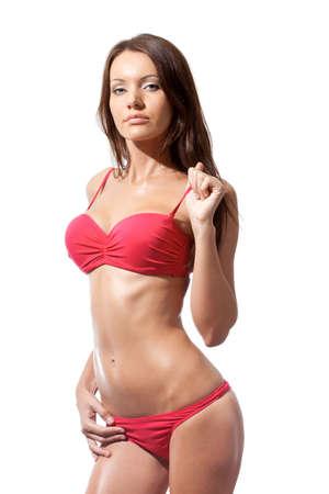 studio shot der sexuellen Frau mit Schultergurt ihrer rosa Bikini über weiße Standard-Bild