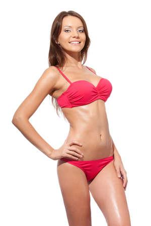 glücklich lächelnde Frau posiert in einem rosa Bikini auf weißem Hintergrund Standard-Bild