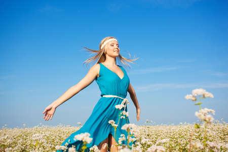beautiful blonde woman walking in a field of flowers, her hair flying in the wind photo