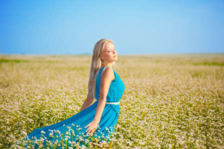 beautiful woman wearing blue dress walking through a field Stock Photo - 15689808