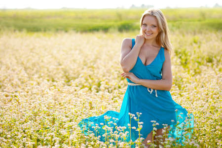 smiling woman wearing blue dress  standing on field of flowers and holding her on hand on abdomen photo