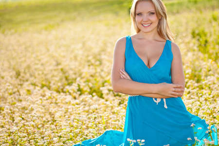 smiling woman wearing blue dress  standing on field of flowers and holding her hands on abdomen Stock Photo - 17613793