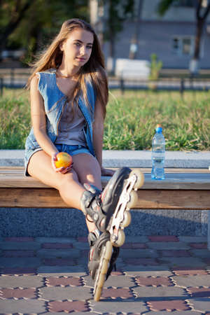 smiling roller  girl wearing jeans vest and shorts sitting on the stairs Stock Photo - 15809913