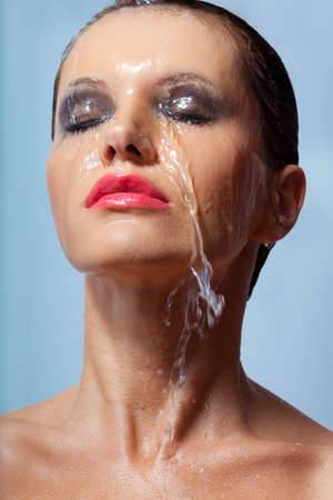 closeup woman face in water over blue background photo